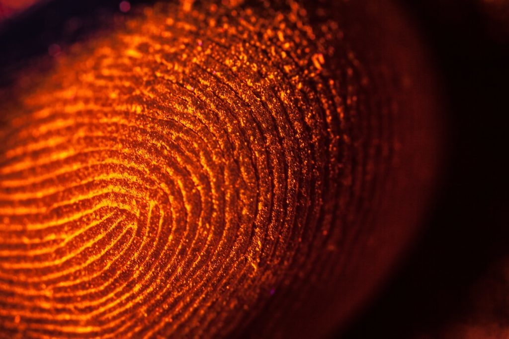 shutterstock_208573624-red-orange-fingerprints-on-black-unfocused