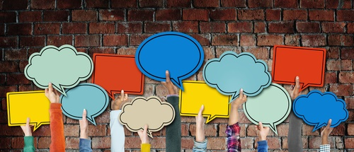 shutterstock_267645518-diverse-hands-holding-colorful-speech-bubbles